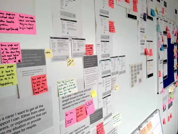 Example of a user research wall with print outs of the service and annotations on post its