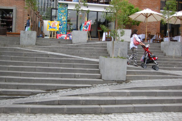 Stair with built in ramp being used by person with pushchair.