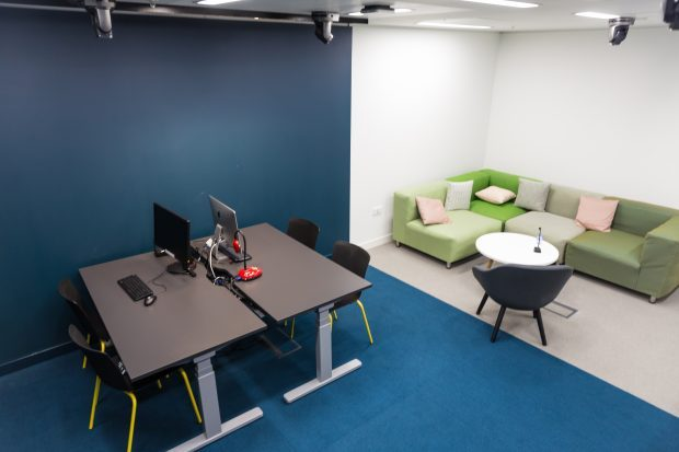 A picture of an empty user research room with sofa, chairs, desks and computers