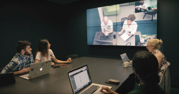 People sitting around a table observing a user research session on a screen
