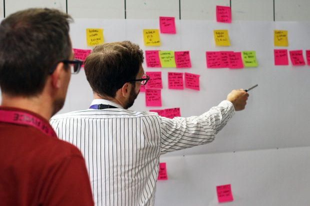 Two people looking at a board with lots of Post It notes attached. One is pointing to one of the notes