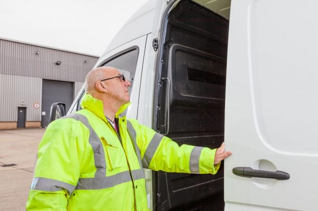 A man wearing a bright fluorescent yellow jacket inspecting the inside of a large white van.