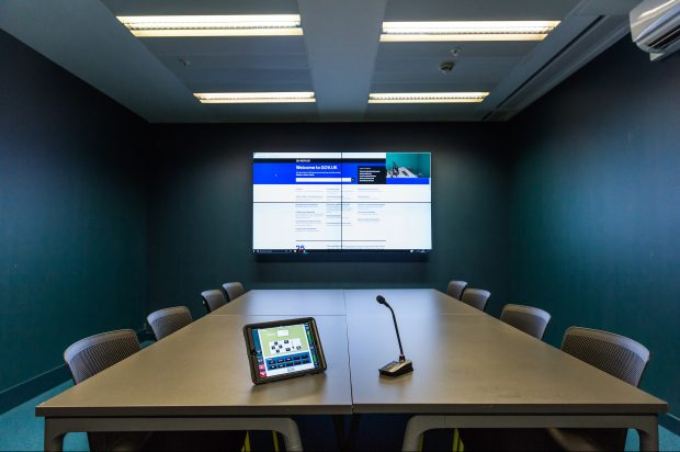One of the user research labs at GDS. The picture shows a large table in the centre of the room, with a tablet and a microphone on it. At the back of the room is a large television screen, on which the website GOV.UK is displayed.