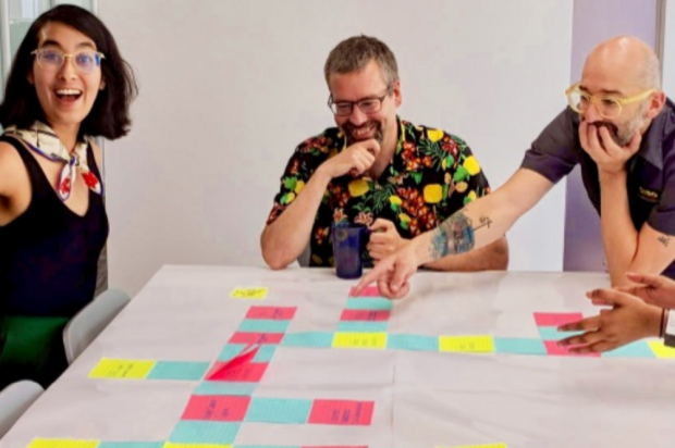 Three members of the Canadian Digital Service, laughing and smiling, around a table on which there is a large assortment of post it notes.