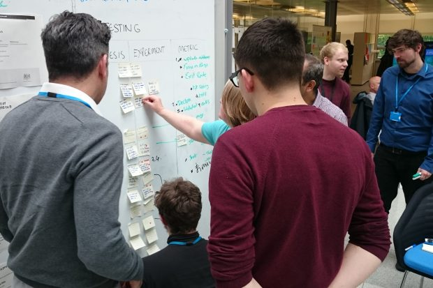 A large team huddled around a white board. There are lots of sticky notes on the board, and a large number of annotations made in black and bright green ink.