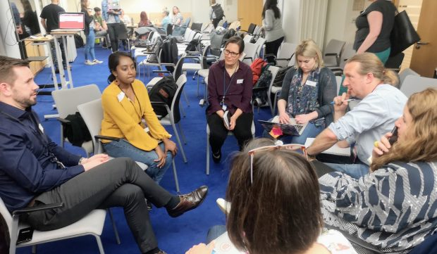 A group of people sitting in a circle having a discussion during the research ethics meetup